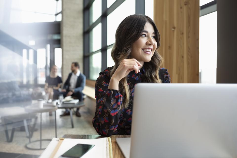 Smiling businesswoman working at laptop