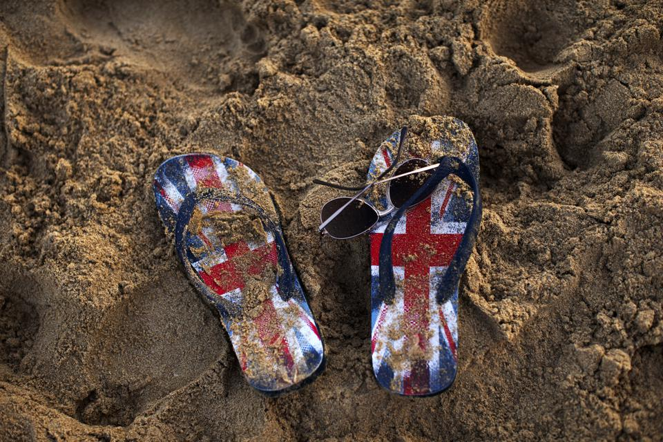 British Union Flag flip-flops in the sand.