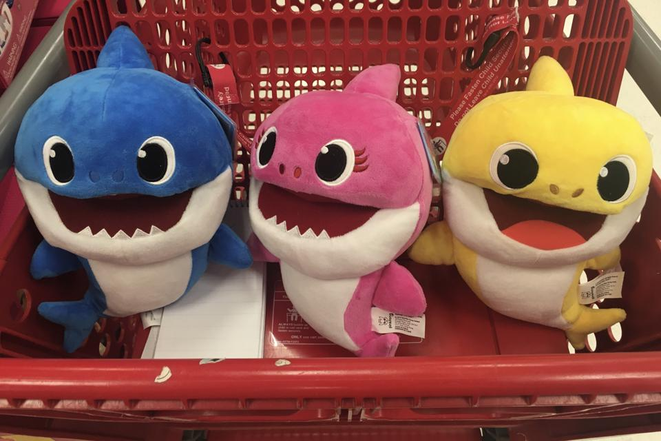 The Daddy, Mommy and  Baby Shark puppets by WowWee in s shopping cart at a Target store.