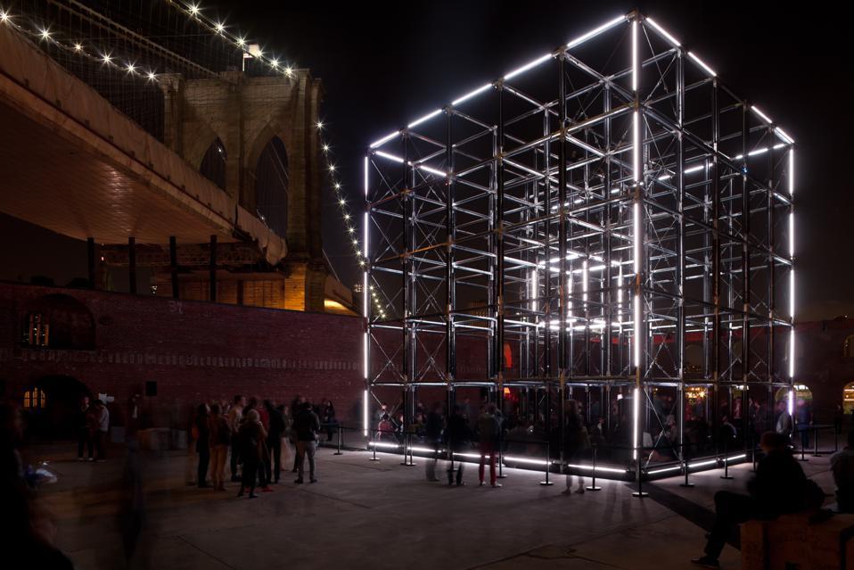 Art installation: A lit-up cube several stories high.