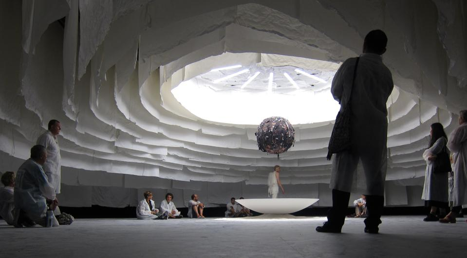 People stand around a dark globe in a massive white tent with light coming through a hole in the center.