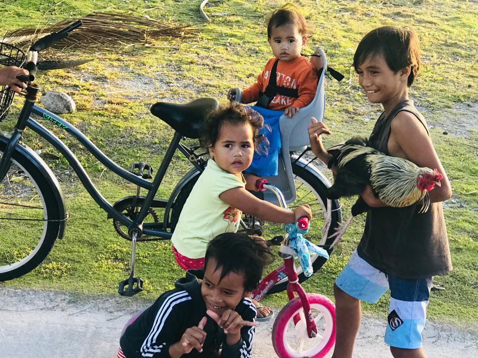 Children with rooster and push bikes