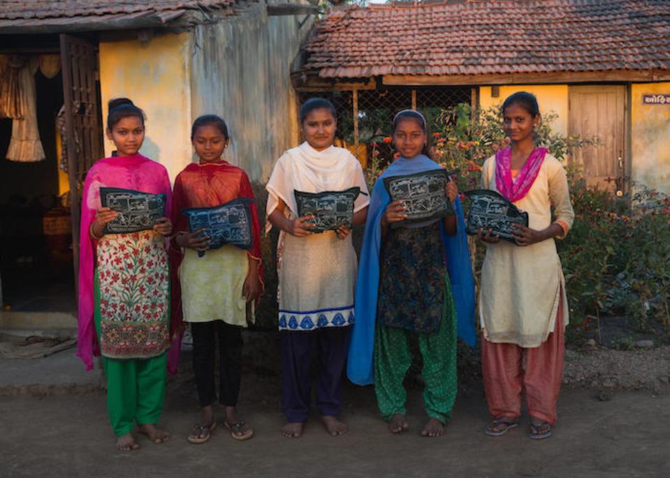 Adolescent girls at a residential ashram school in Khamar Village in Gujarat, India hold menstrual hygiene kits they received from UNICEF partner organization Seva Rural.