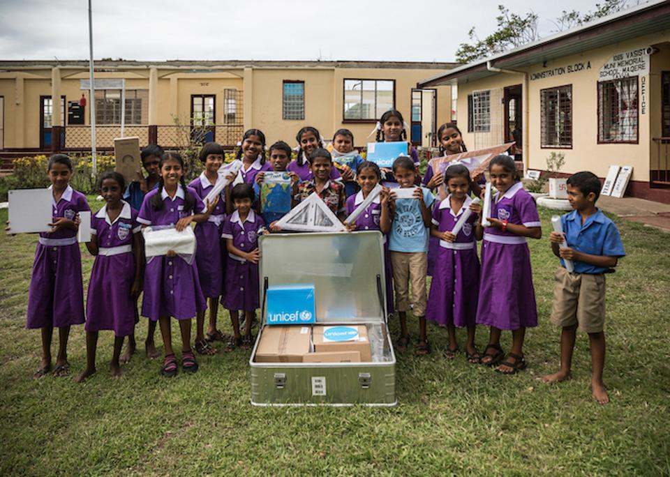Students of Vasist Muni Municipal School in Fiji display the contents of a School-in-a-Box kit provided by UNICEF.