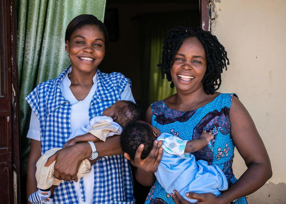 UNICEF-supported health worker Amilia Mathew (left) and her sister hold twins delivered at their local clinic  in Yola, Nigeria.