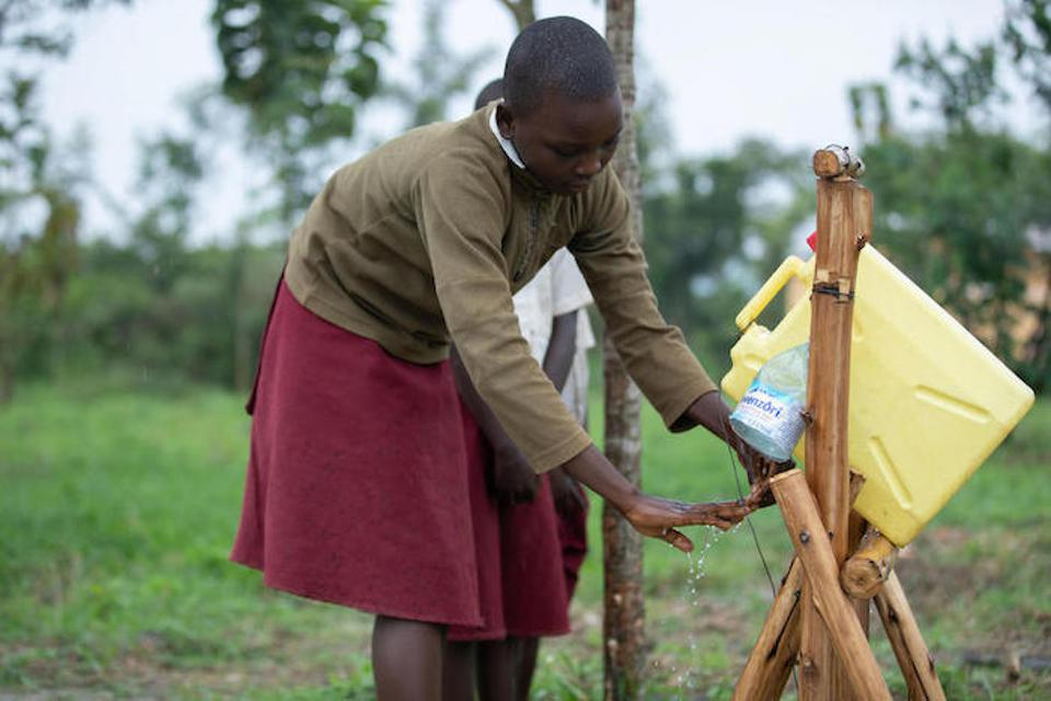 A student washes her hands at a locally made tippy tap outside Damasiko Primary School in western Uganda's Kamwenge district.