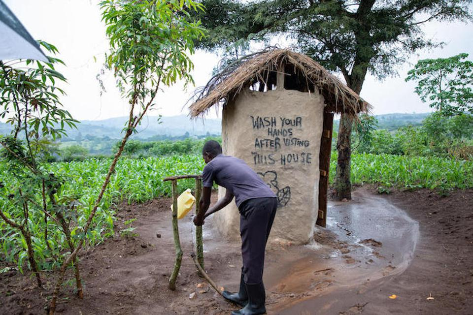 After attending a sensitization session, Nsemerirwe Aarons upgraded his family's latrine, plastering the walls and adding doors and a tippy tap for handwashing.