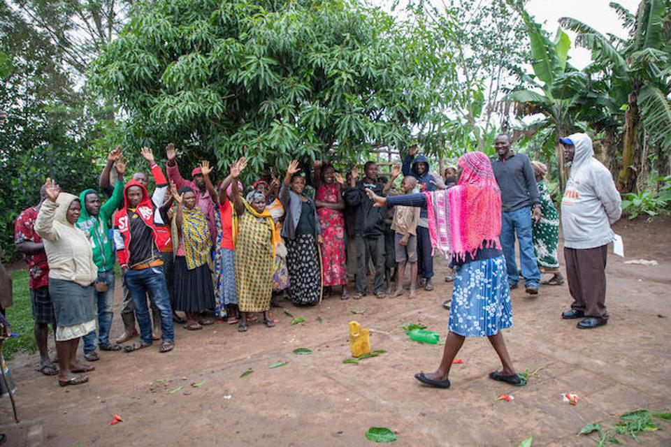 Health workers do a ″walk of shame″ with a group of villagers using a map on the ground identifying open defecation spots in their village in Kamwenge district, Uganda.