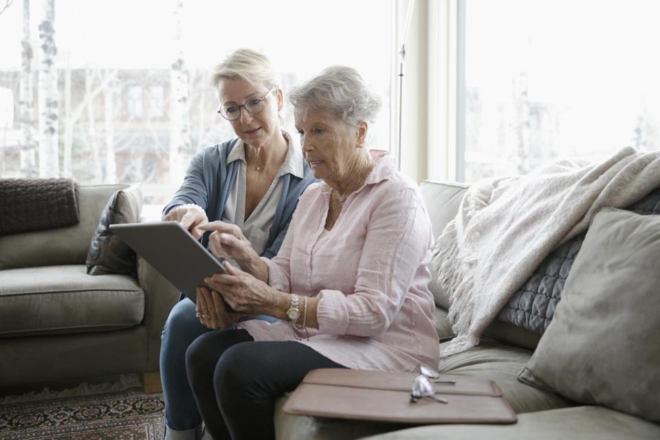 Daughter helping senior mother using digital tablet