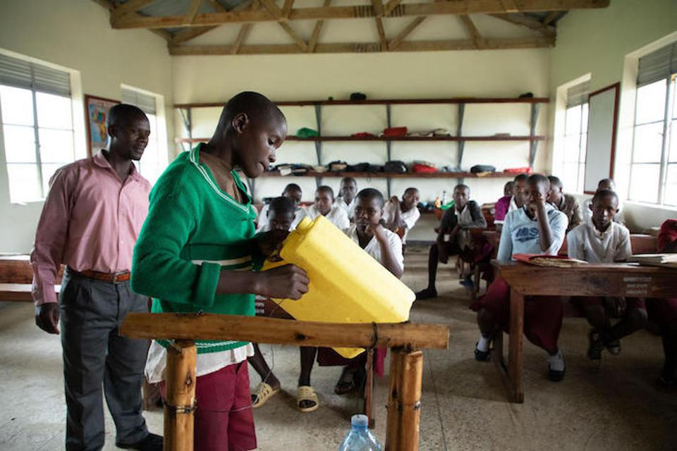 A young health worker teaches students at Damasiko Primary School how to make and operate a tippy tap.