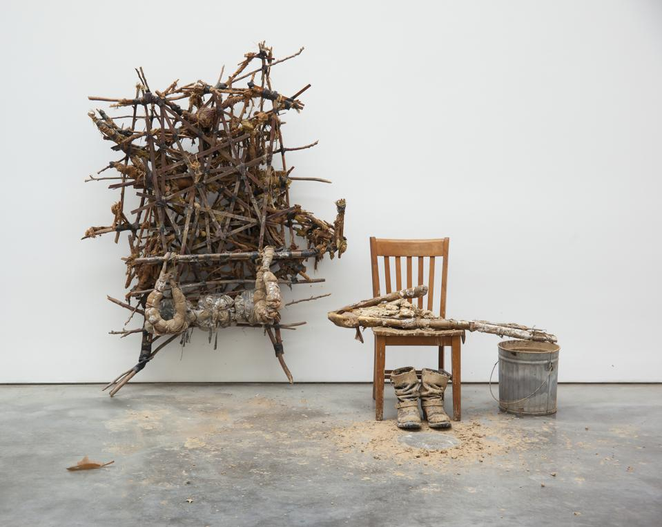 Kim Jones, Mudman Structure (large), 1974, sticks, mud, rope, foam rubber, shellac, and acrylic; shown with chair, boots, and bucket of mud.