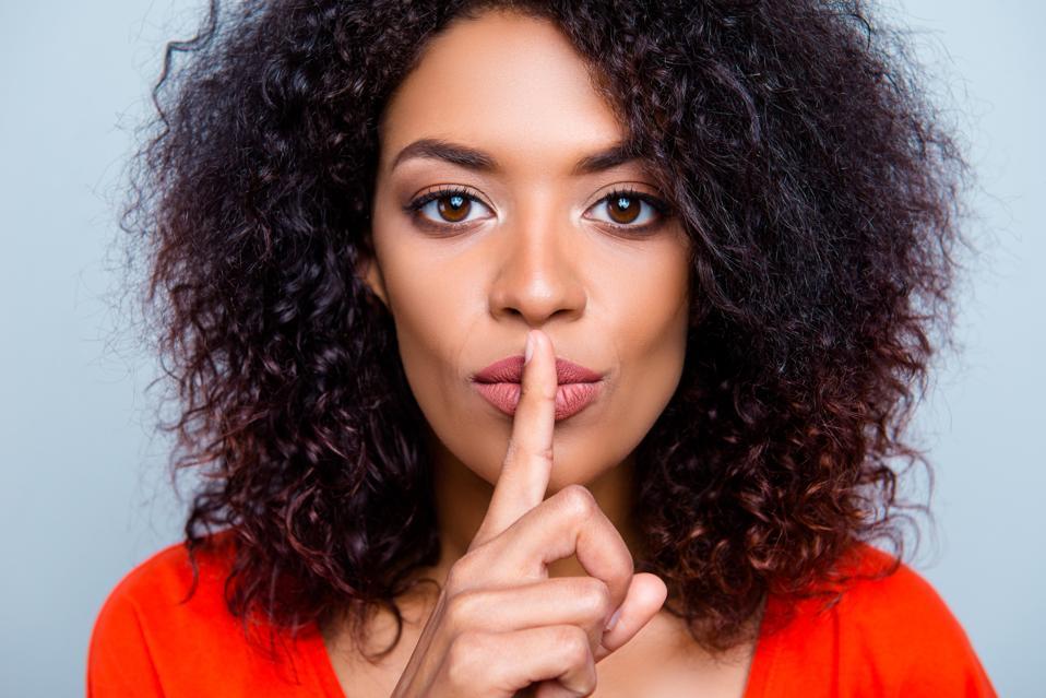Schh! Nahaufnahmeporträt der mysteriösen hübschen Frau mit moderner Frisur bittend um das Halten der Ruhe, die Zeigefinger auf den prallen Lippen lokalisiert auf grauem Hintergrund hält