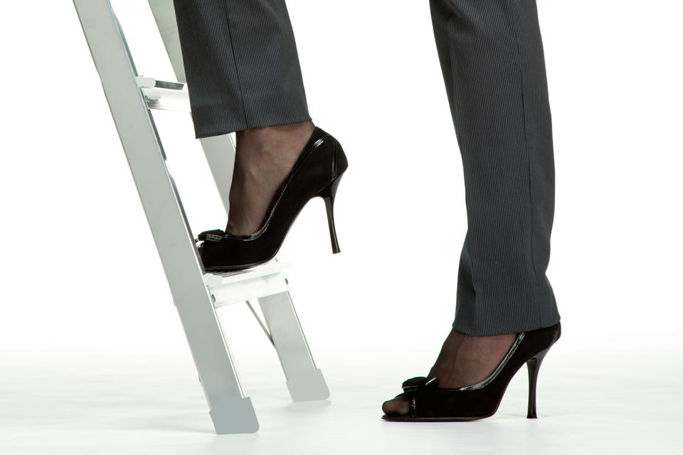 Woman stepping up ladder in heels
