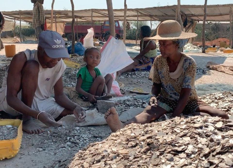 In Madagascar, a man, woman and child sift through piles of rock for mica, the silvery mineral composite used in the production of everyday items like makeup and paint.