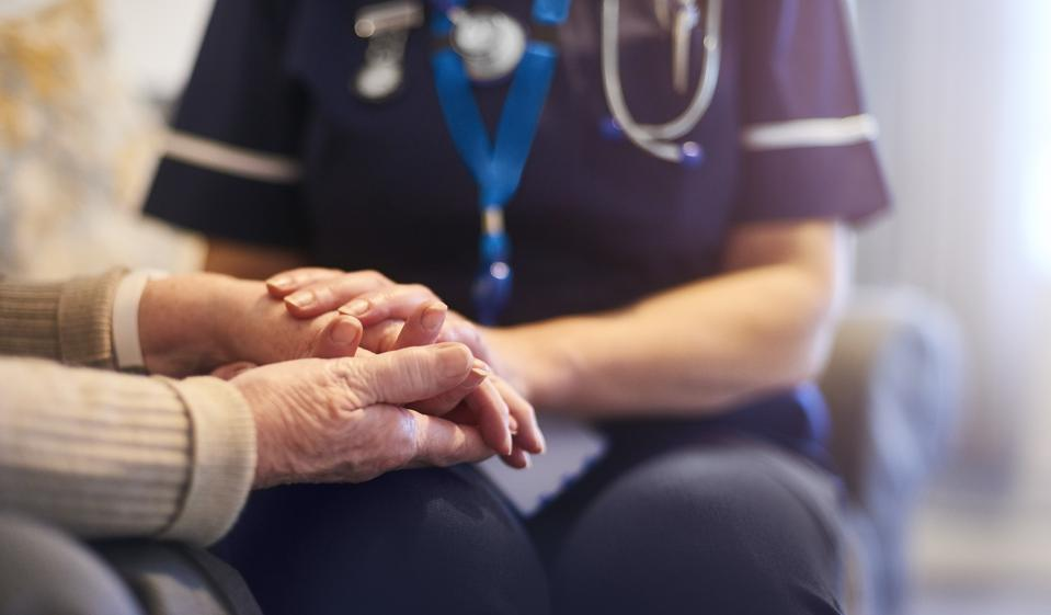 Nurse comforting patient at patient's home