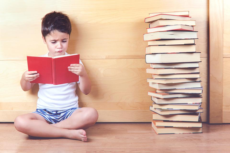 Boy Reading Book While Sitting On Floor Against Wooden Wall