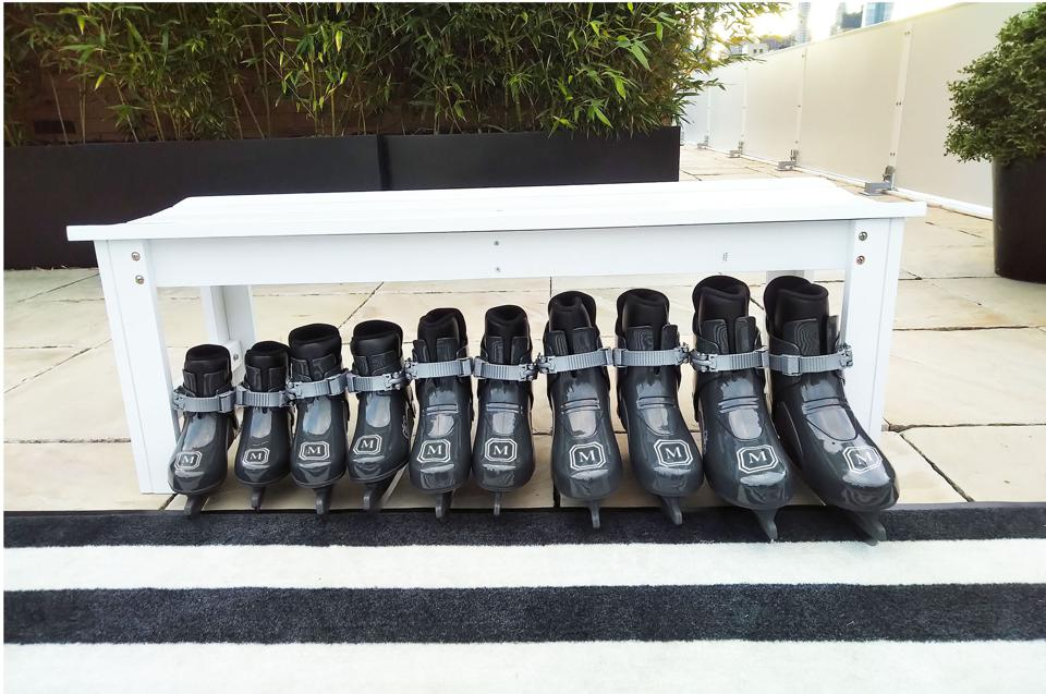 The Mark's skating rink boots line up under bench.