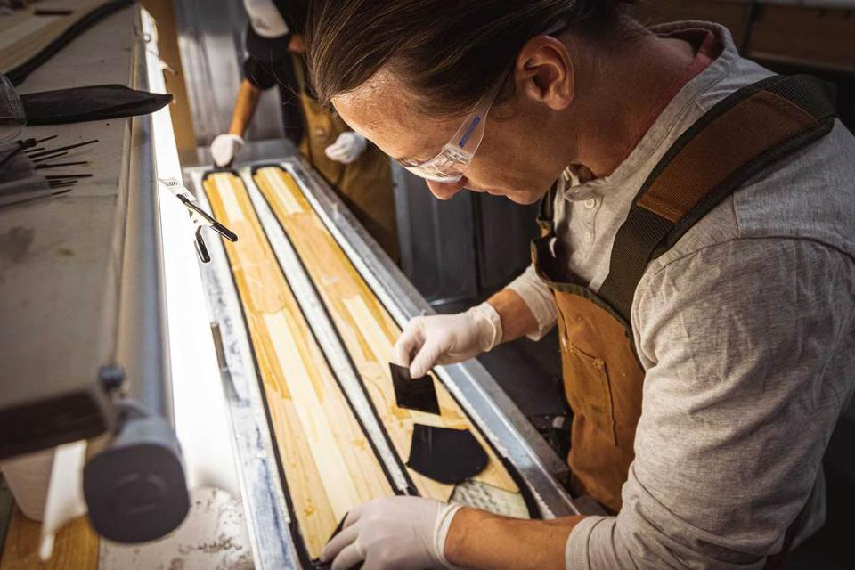 A man hand-assembling a ski in a workshop.