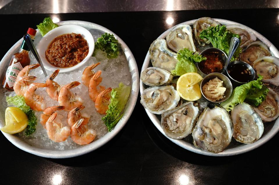 Plate of raw oysters and a plate of cooked shrimp on ice.