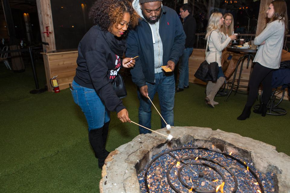 An African American couple roasting marshmallows over an indoor fire pit.