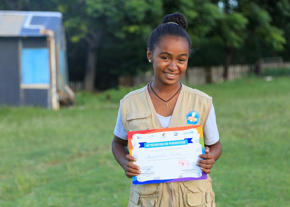 Christella proudly displays her reporter's training certificate. She's well on her way to realizing her dream of becoming a journalist. ©