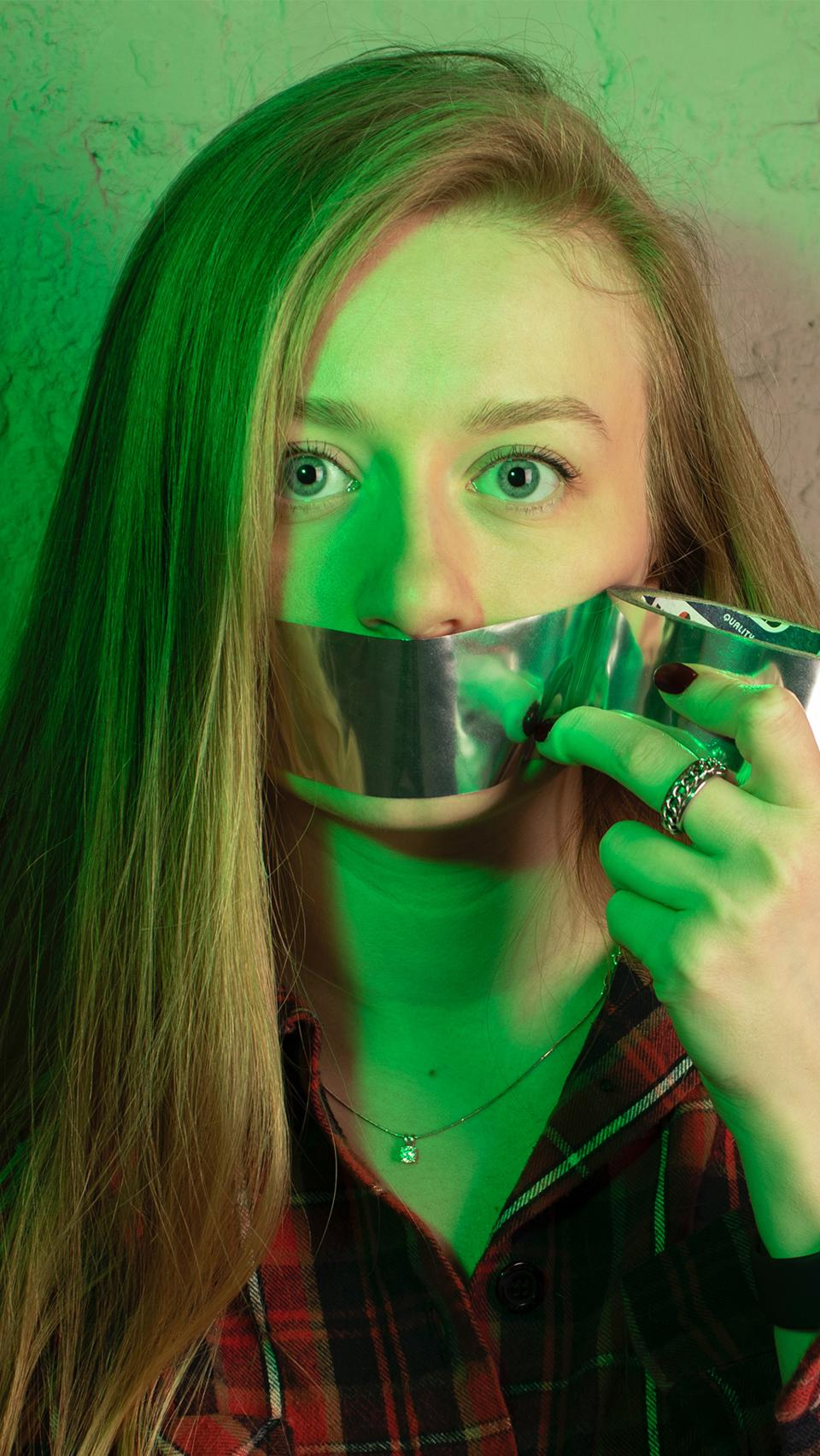 A young woman tapes her own mouth in a self-censorship attempt