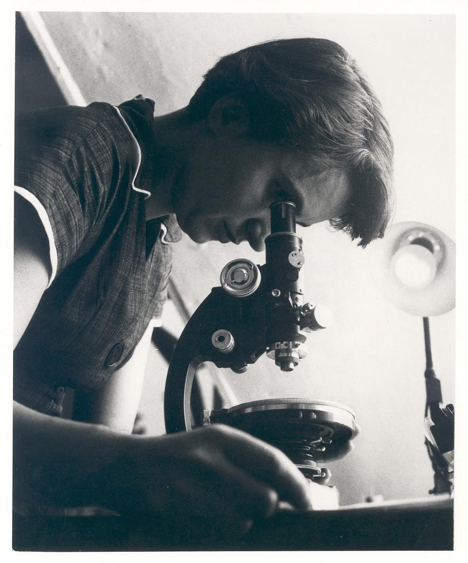 Woman at microscope.