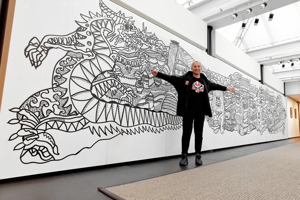 Russian artist Max Goshko-Dankov aka MGDankov next to his Coloring Wall in Beijing