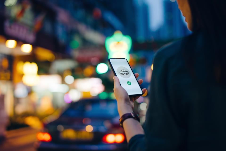 Over the shoulder view of woman using mobile app on smartphone to arrange taxi ride in downtown city street, with busy traffic scene as background