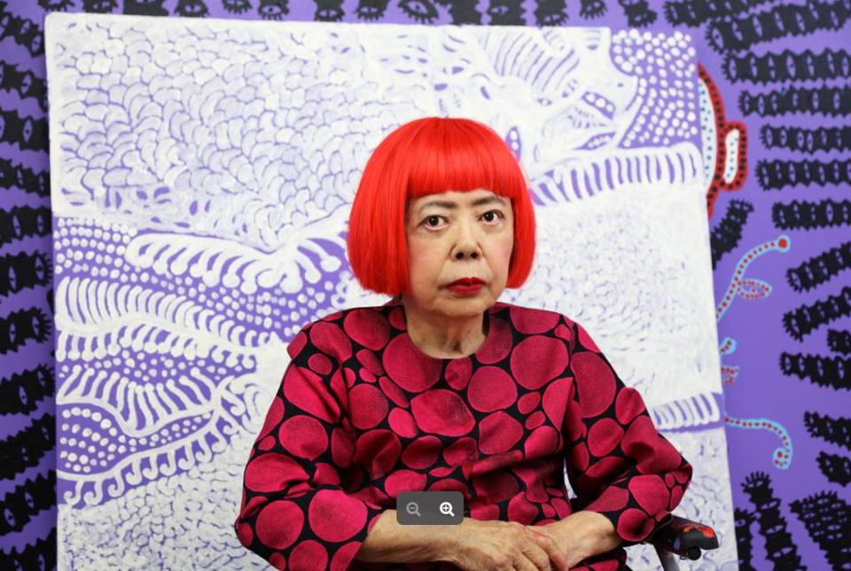Yayoi Kusama in front of two of her recent paintings.