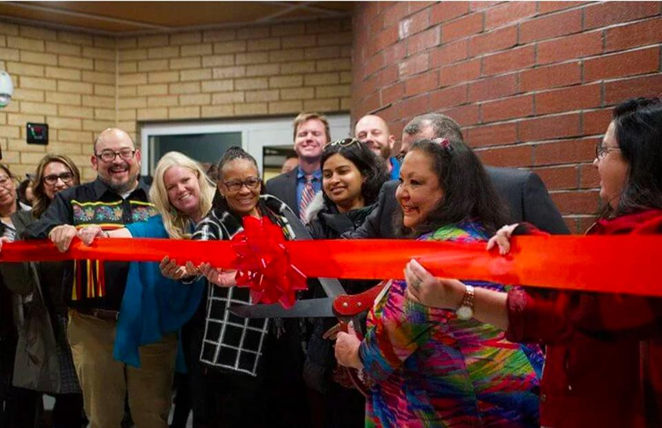 Executive director of the Ain Dah Yung Center, Deb Foster, is joined by contributors at the ribbon cutting of Mino Oski Ain Dah Yung, an affordable housing development serving American Indian youth in St. Paul, Minn.