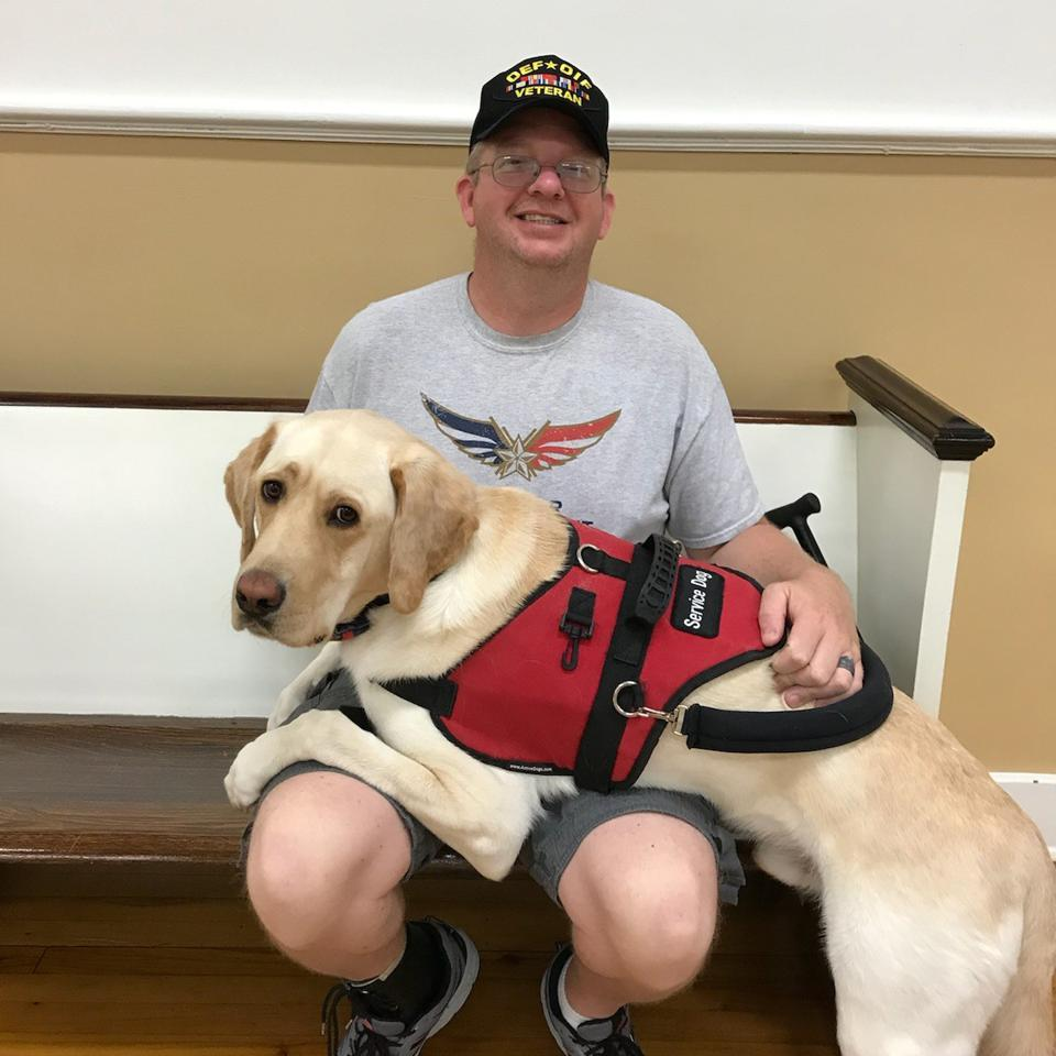 Paws with Purpose Beneficiary sits with his therapy dog.