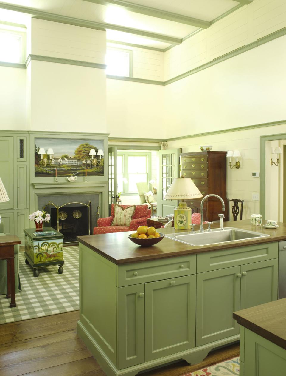 green painted cabinets, and an island characterize this open kitchen with high ceilings and lots of windows.