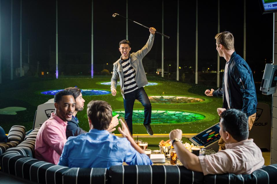 Man holding golf club in the air at Topgolf.
