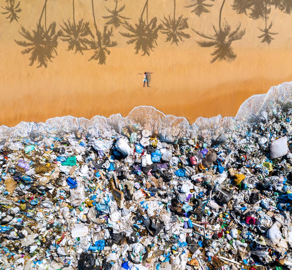 Man lying on the beach with garbage in the water. Ocean pollution concept with plastic and garbage