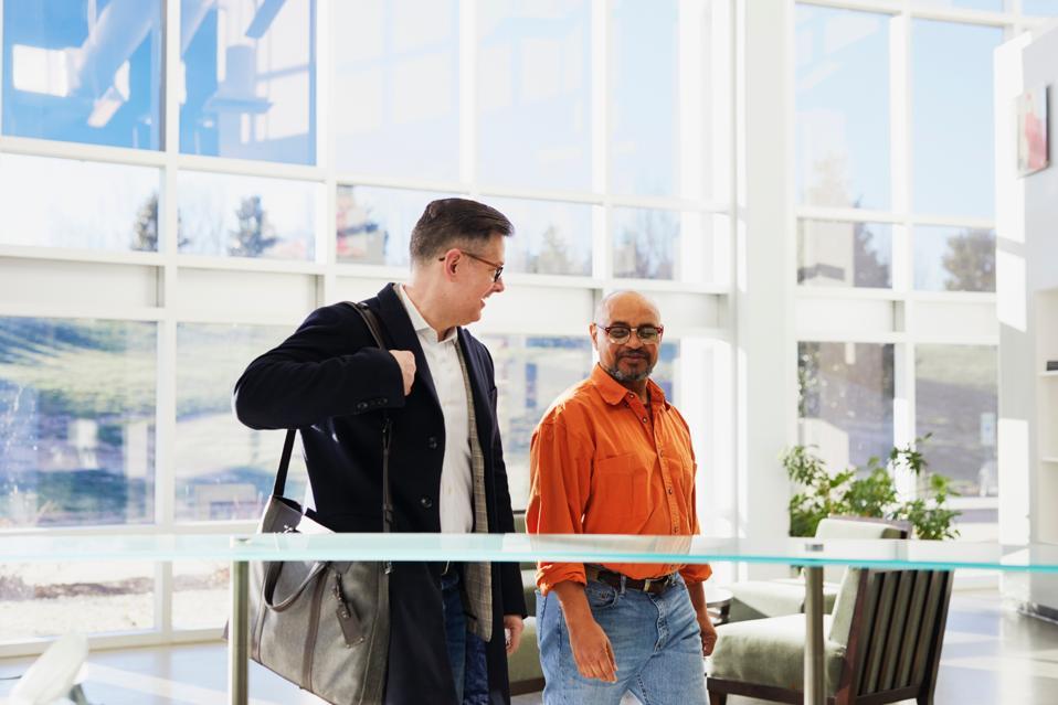Two men talk while walking through a building lobby.