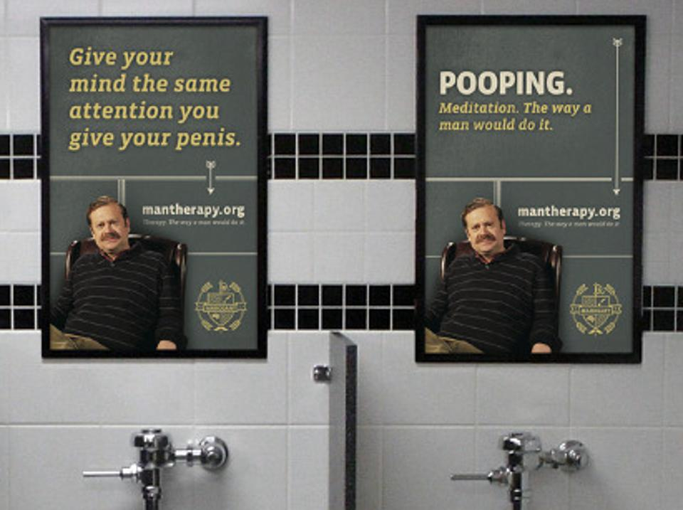 Two Man Therapy posters are displayed in a restroom.