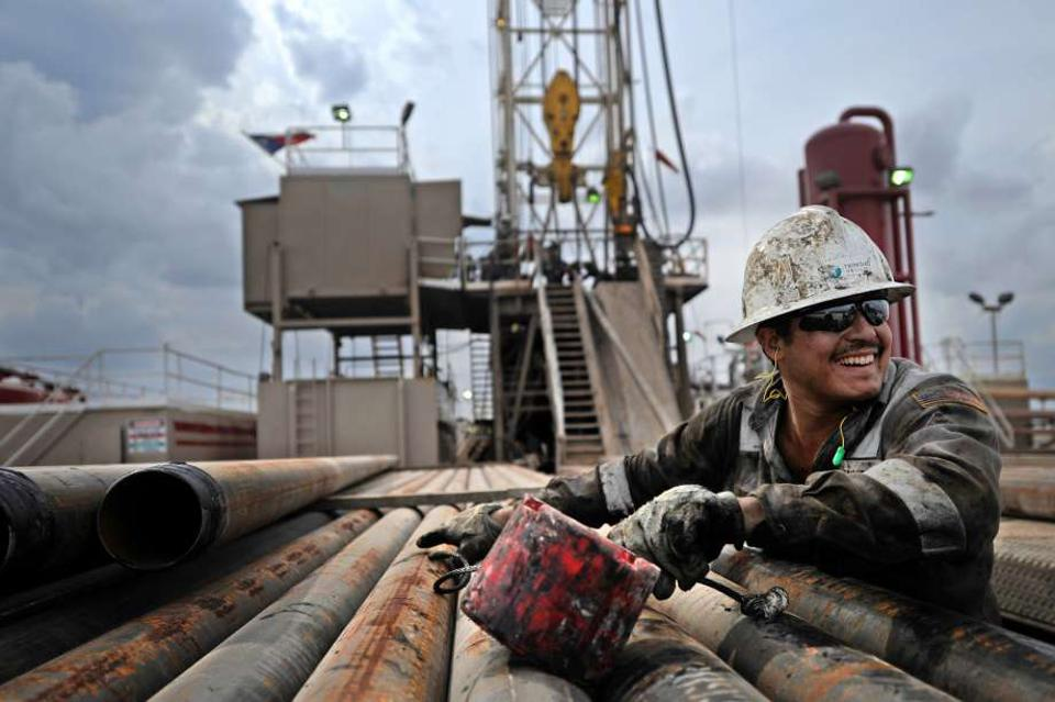 A floorhand moves casing on a rack beside his Permian drilling rig (Midland, Texas)