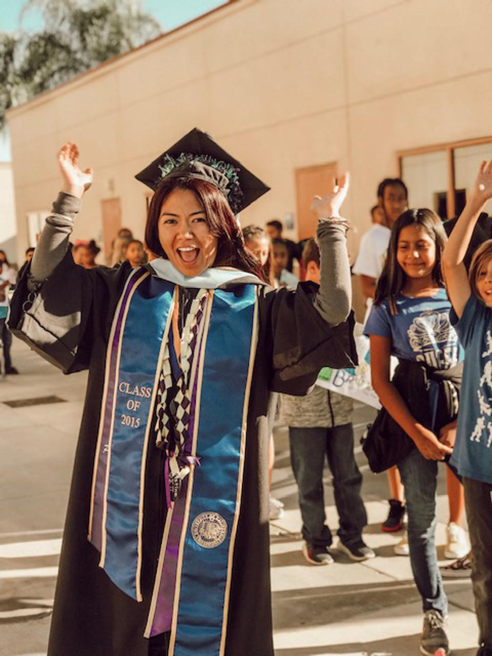 A teacher in graduation robes stands with her elementary students.