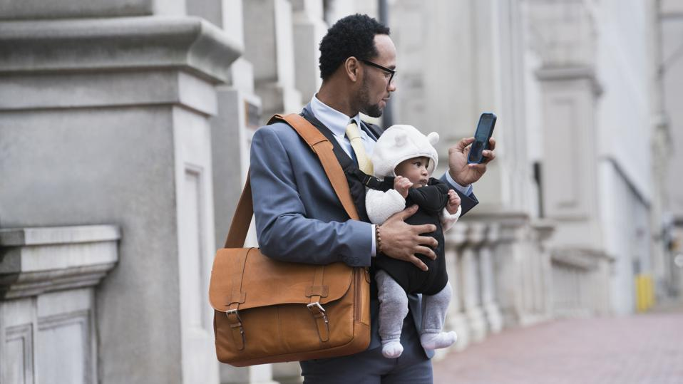 Businessman with son in baby carrier texting on cell phone