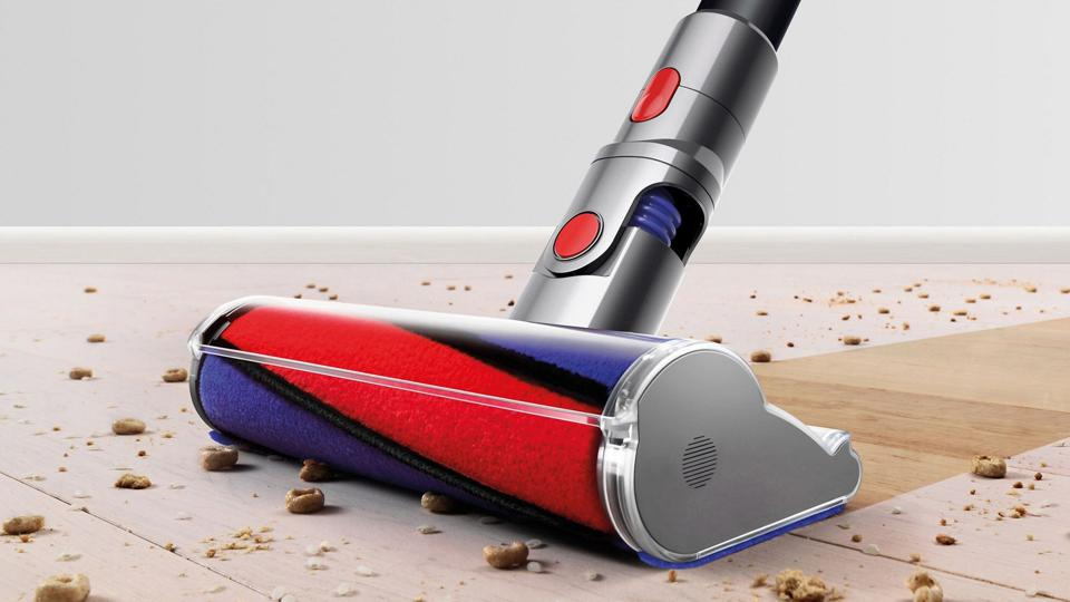 Dyson V10 vacuum cleaning a dirty floor.