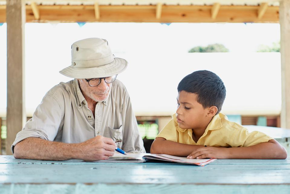 An OLLI student works with a Belizean child.