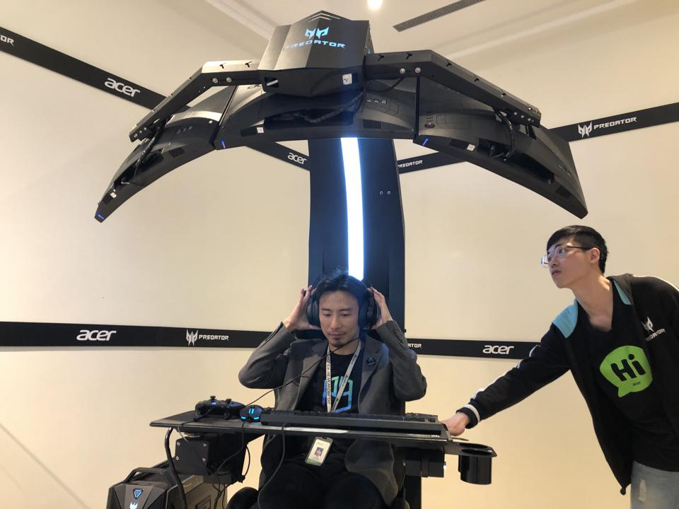 Andrew Chuang, left, Acer's eSports GM, gets ready to use a $30,000 gaming machine at the company showroom near Taipei, November 22, 2019.