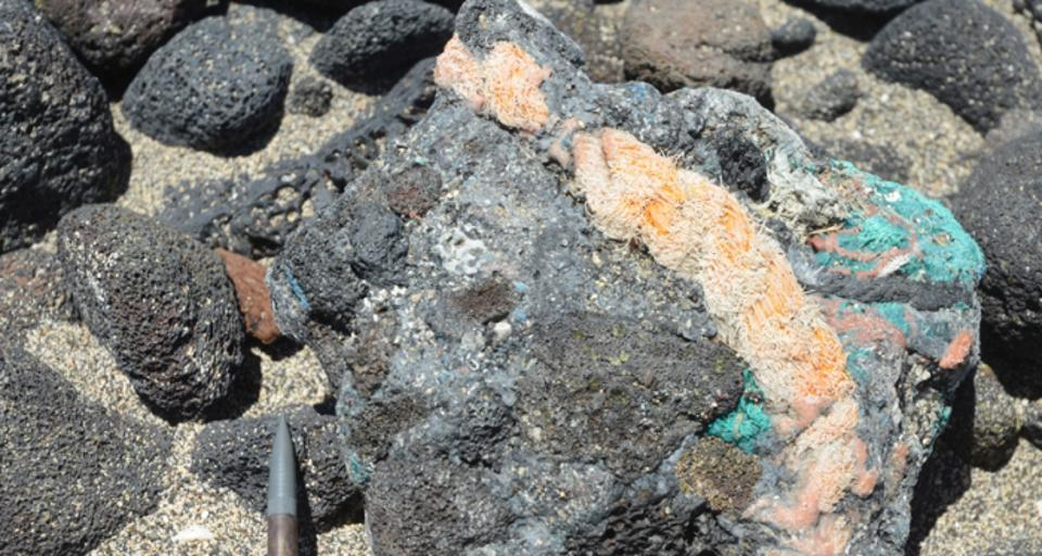 Example of a newly named rock, called plastiglomerate, made of lava rock, green and red netting, yellow rope and melted plastic.