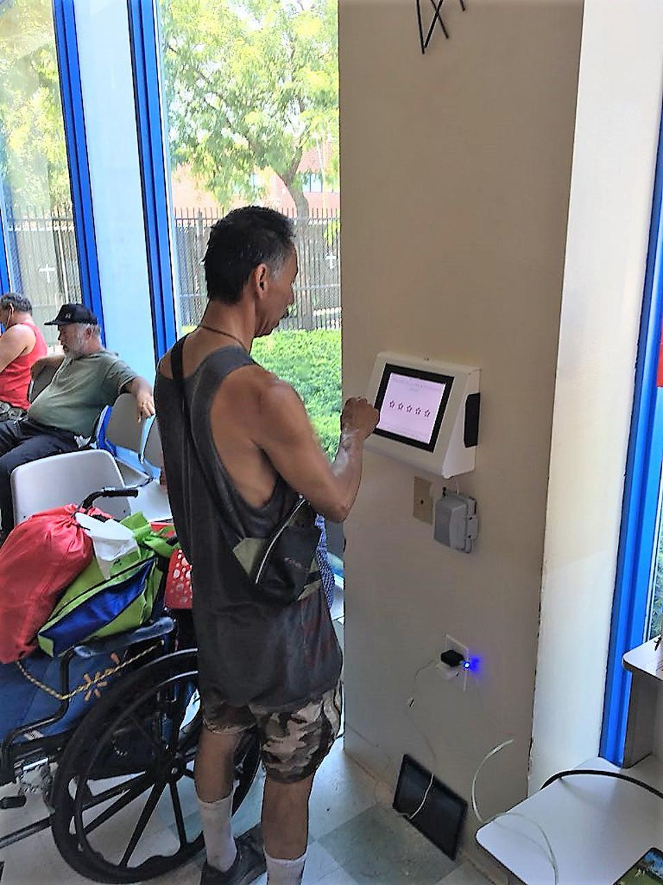 Patron uses Pulse For Good kiosk to offer feedback.