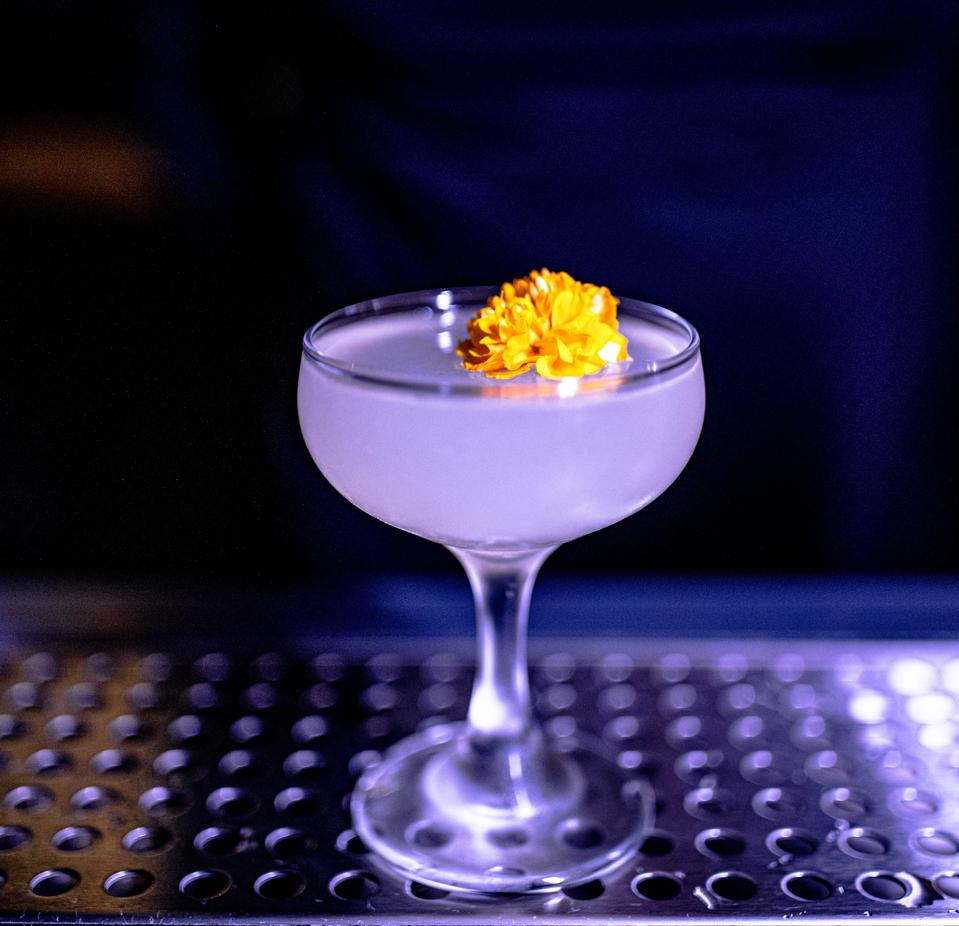 Cocktail in a coupe glass, garnished with a small, yellow flower.