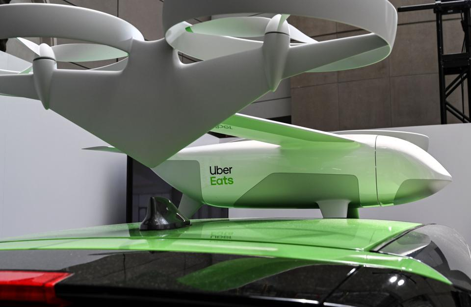 An Uber Eats car and drone on exhibit at the Uber Elevate Summit 2019. Uber said Wednesday it plans to speed up restaurant meal delivery by using drones for its Uber Eats service. For logistical reasons, the drones will not deliver directly to customers, but to a safe drop-off location where an Uber Eats driver will complete the order. In the future, Uber hopes to land the drones on parked vehicles located near each delivery location to allow the final delivery by hand. Uber said it had developed a proprietary airspace management system called Elevate Cloud Systems that will guide the drones to their location. EVA HAMBACH/AFP/Getty Images