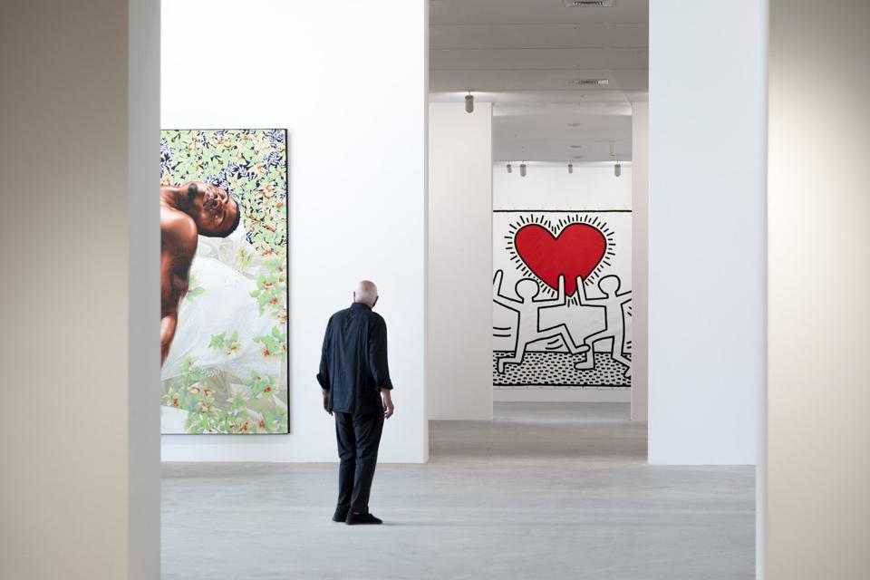 Don Rubell inside the newly opened Rubell Museum in Miami, (left to right) Kehinde Wiley, 'Sleep', 2008 oil on canvas, 132 x 300 in. (335.3 x 762 cm), and Keith Haring, 'Untitled,' 1981. Enamel on fiberboard. 48 x 48 in. (121.9 x 121. 9 cm). ©Keith Haring Foundation.