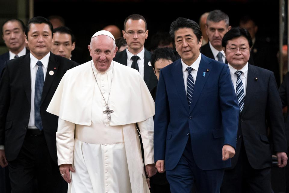Pope Francis walks with Japan's Prime Minister Shinzo Abe.