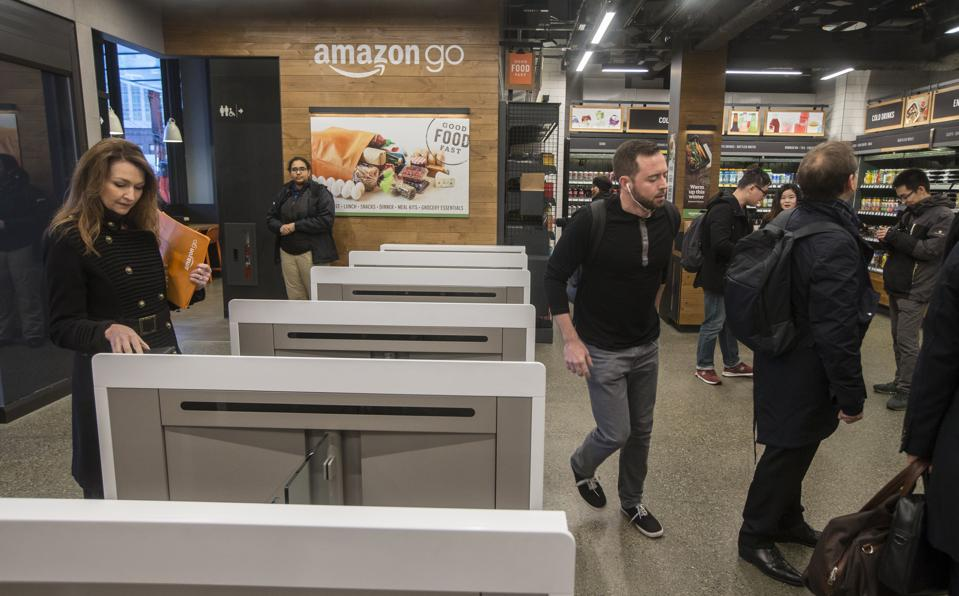 Shoppers scan the Amazon Go app on their mobile devices as they enter the Amazon Go store in Seattle, Washington. Photo by Stephen Brashear/Getty Images